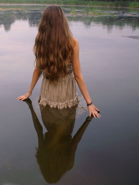 A long-haired girl standing in a calm pool of water