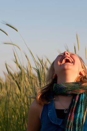 A woman laughs while sitting in tall grass